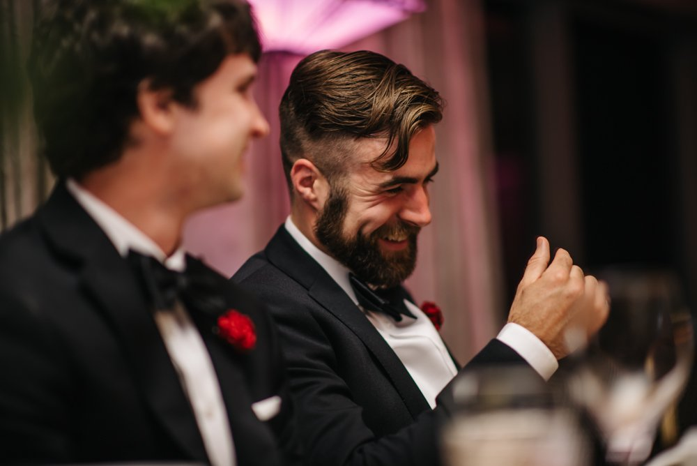 groomsman laughing during wedding reception in Banff Alberta