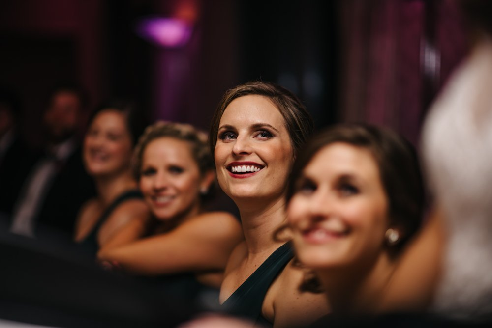 smiling during speeches at wedding in Banff Alberta
