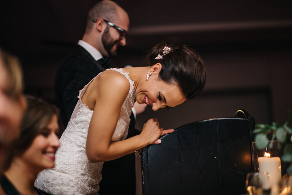 bride laughing during bride and groom speeches at a wedding in Banff Alberta