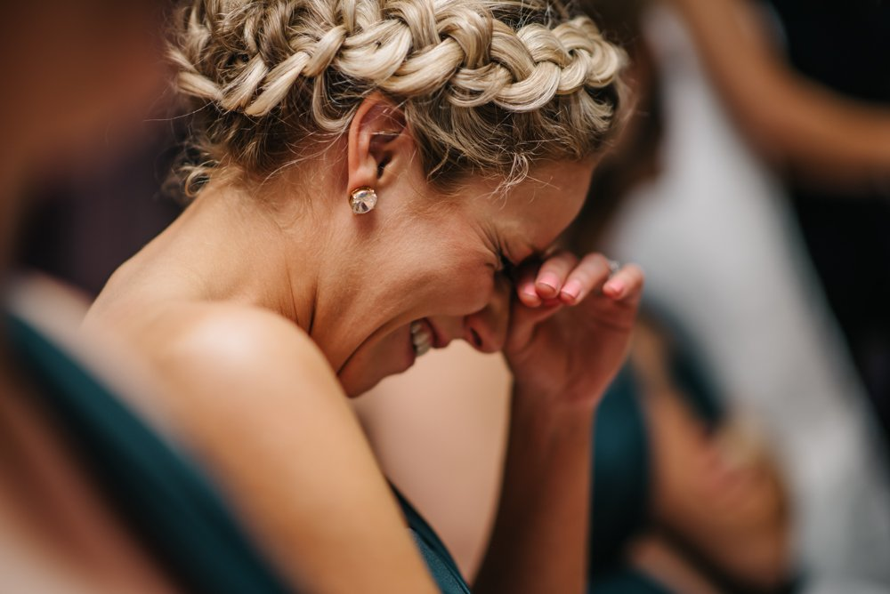 Bridesmaid laughing during speeches at a wedding reception in Banff Alberta