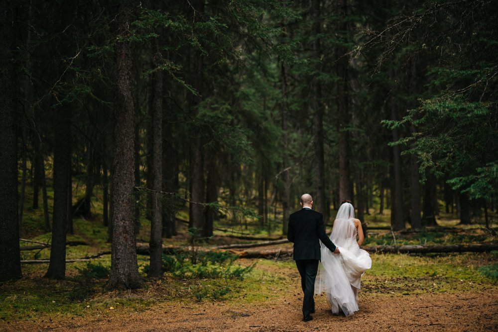 bride and groom walking through the forest in Banff
