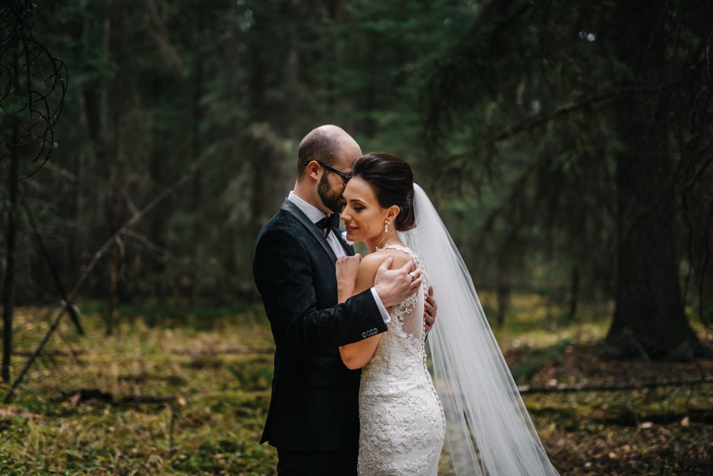 bride and groom cuddling in the forest in banff