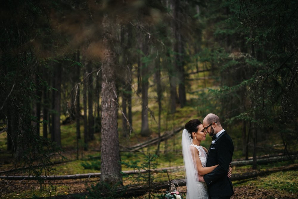 bride and groom in the forest in Banff at the rimrock