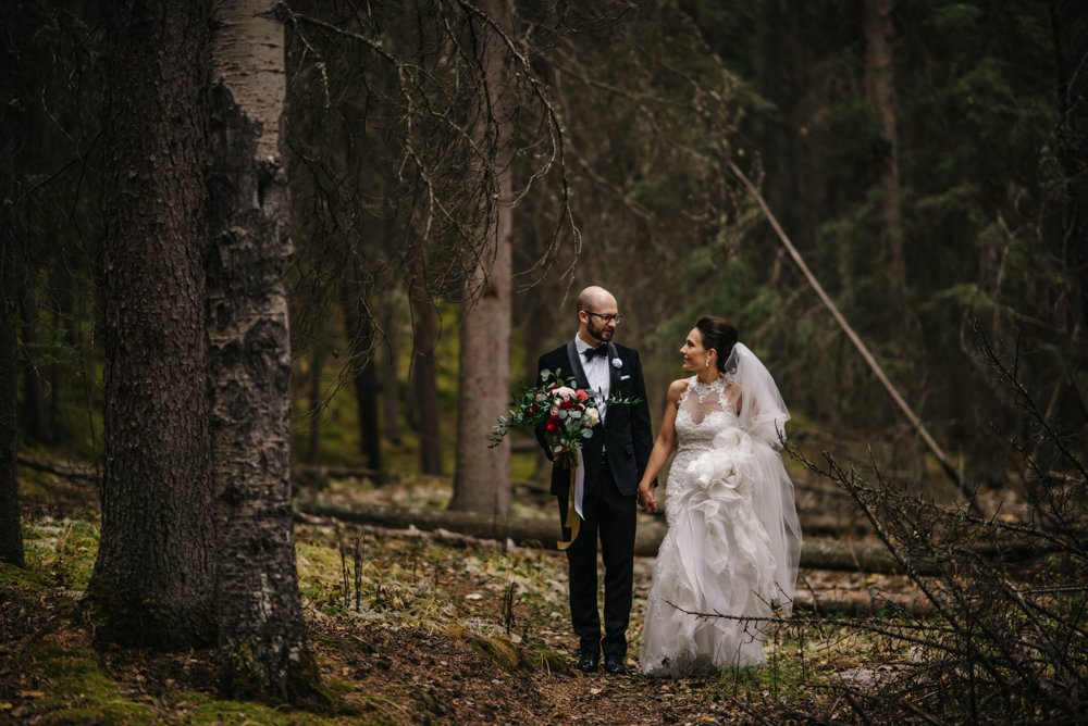 bride and groom walking through the forest in the rain in Banff
