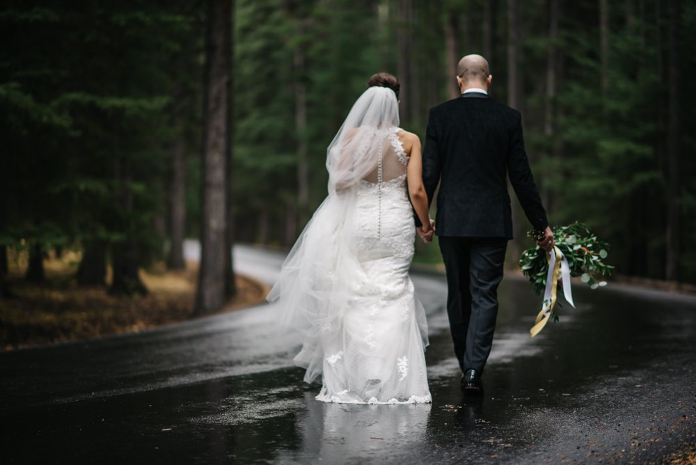 bride and groom walking in the rain for wedding photos