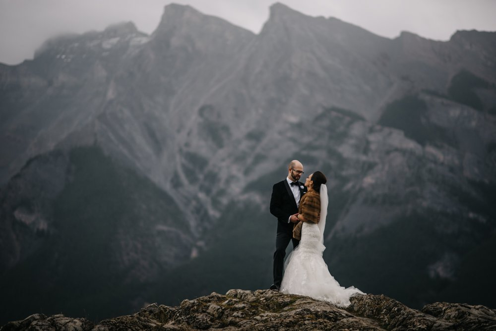 bride and groom standing on a mountain in Banff