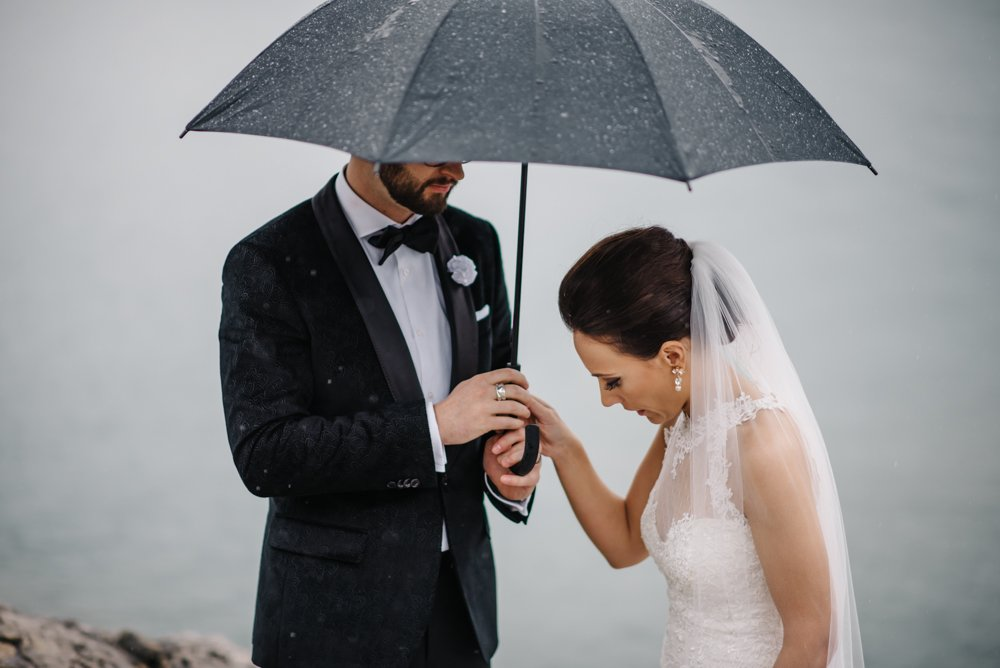 bride and groom wedding photos in the rain
