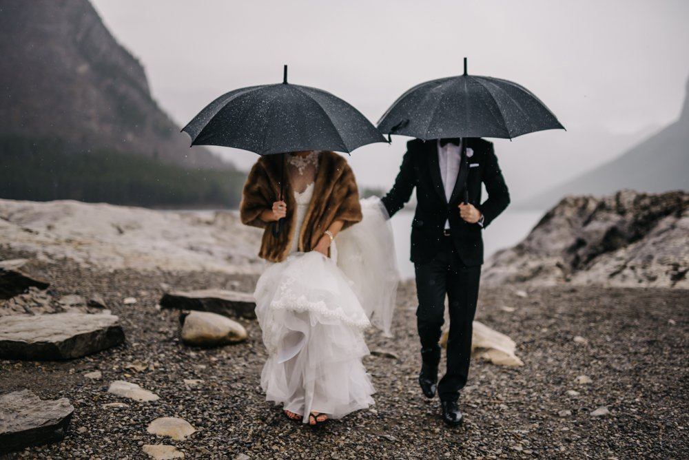 bride and groom walking in the rain in Banff