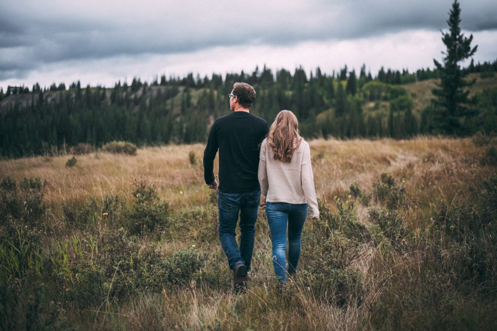 Couple walking candid during their engagement session in the mountains